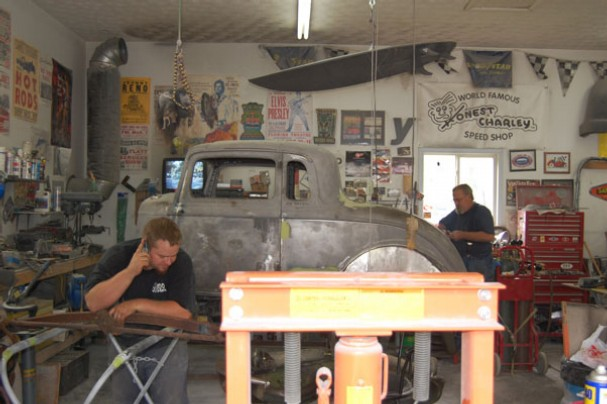two men working in a crowded garage, rebuilding an antique car