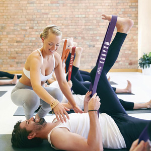Woman helping man stretch using resistance bands