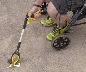 the HMS Grabber reacher being used by a person in a wheelchair to pick up keys