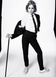 B&W photo of Selma Blair wearing a black suit, white shirt and black tie, and black cane