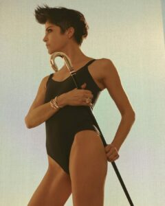 Selma Blair stands in 3/4 profile wearing a black one-piece bathing suit and holding a black cane with a tan handle